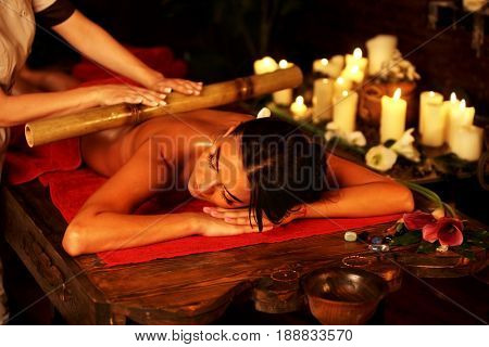 Bamboo massage of woman in spa salon. Girl on candles background in massage spa salon. Luxary interior in oriental therapy salon. Female have relax big stick on red towel.