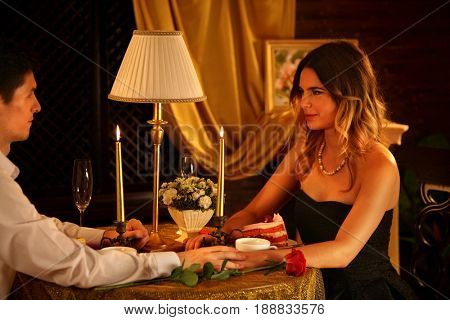 Romantic dinner for couple. Restaurant interior with candlelight for romantic date. Happy people in love. Girl gently looks at her boyfriend. Pictures in room. Declaration of love.