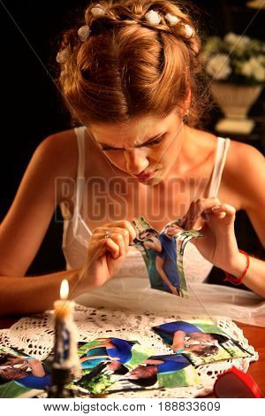 Sad bride on unhappy wedding. Woman and groom quarrel. Girl in white dress tearing family pictures. Portrait crying female. Candle and wedding ring are on table on black background.