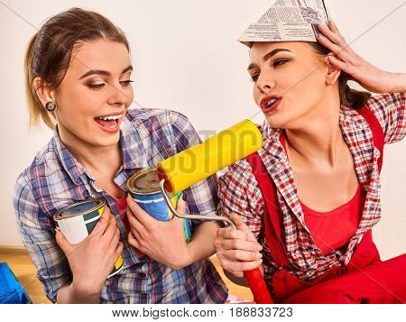 Repair home women holding painting tools roller for wallpaper. Happy girls wearing newspaper hat renovation apartment in room.