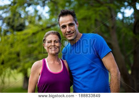 Portrait of couple with arms around in park