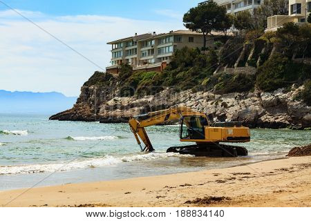 View of the empty beach with the working excavator. Salou, Spain