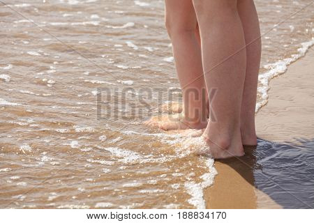Closeup shot of the feet of mother and her child in water beach
