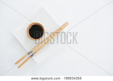 Chopstick and soy sauce on white plate against white background