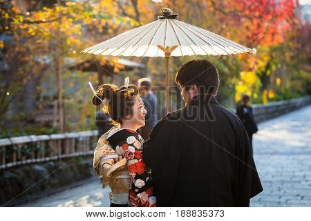 KYOTO, JAPAN - NOVEMBER 11, 2016: Japanese couple wearing traditional japanese kimonos walk on the street of Gion, Kyoto old town, Japan. Kimono is a Japanese traditional garment.