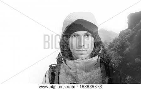 Portrait of a man hiker with backpack on the background of a mountainous rocky landscape. The double exposure effect.
