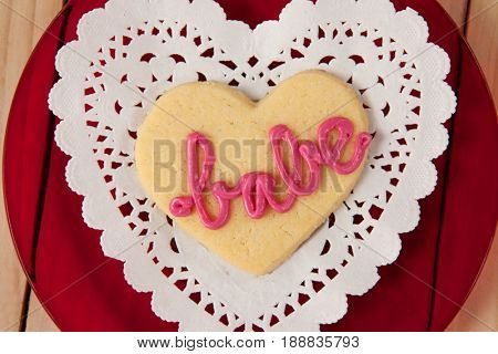 Close-up of heart shaped cookie iced with pink cream in text babe on wooden table
