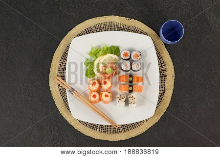 Assorted sushi set served with chopsticks and glass on sushi mat against black background