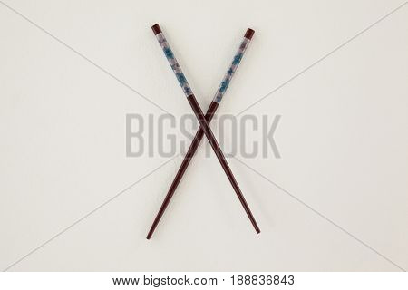Pair of patterned chopsticks against white background