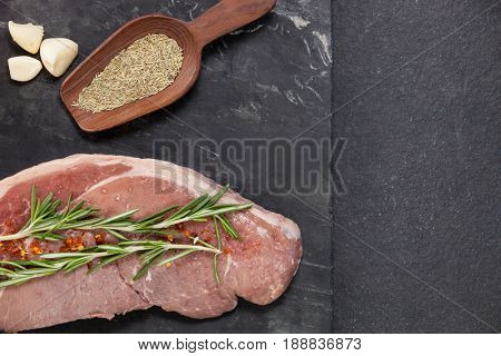 Sirloin chop, garlic and spices on black slate plate against wooden background