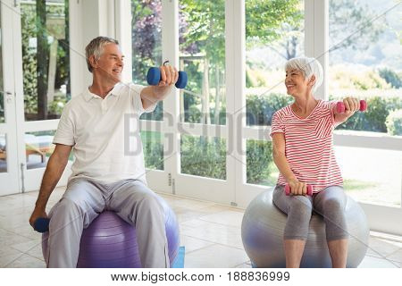 Senior couple exercising with dumbbell on exercise ball at home