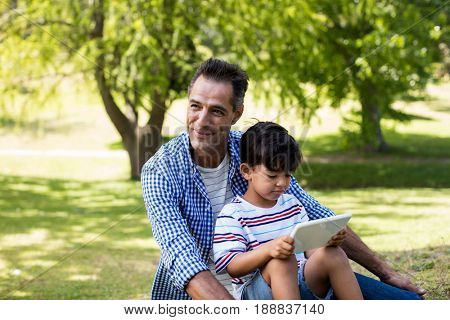 Boy sitting on his fathers lap and using digital tablet in park on a sunny day