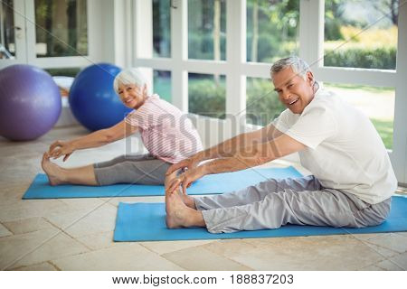 Senior couple performing stretching exercise on exercise mat at home