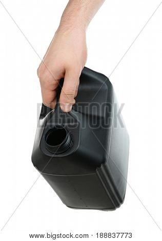 Human hand pouring out oil from black plastic jerrycan on white background