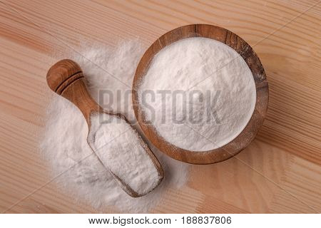 Top view of bowl and scoop with baking soda on wooden table