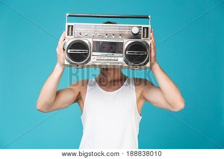 Photo of young man standing over blue isolated background covering face with tape recorder.