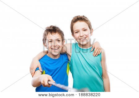 Two handsome smiling child boy brothers hand holding mobile phone or smartphone selfie stick taking portrait photo white isolated