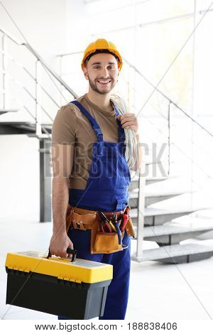 Young smiling electrician holding bunch of wires and toolbox in light room