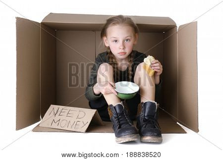Poor little girl sitting in cardboard box and begging for money on white background