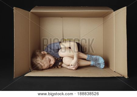 Poor little girl lying in cardboard box on black background
