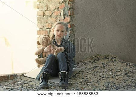 Sad little girl with toy bear sitting near derelict building outdoors. Concept of poorness