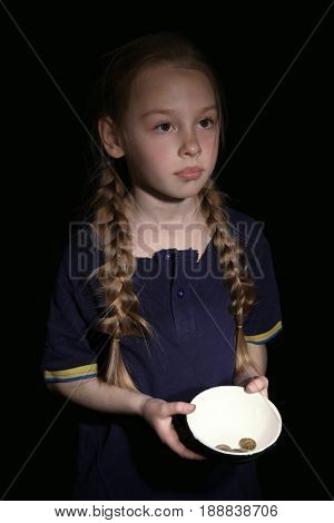 Poor little girl holding bowl with coins on black background