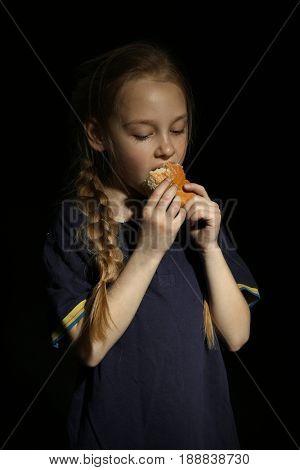 Poor little girl eating bread on black background