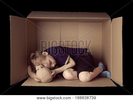 Poor little girl sleeping in cardboard box on black background