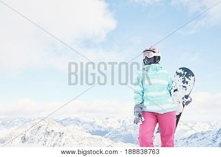 Female snowboarder wearing colorful helmet, blue jacket, grey gloves and pink pants standing standing with snowboard in her hand and preparing for ride - snowboarding concept, copy space