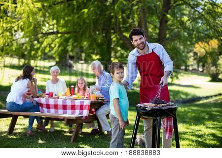 Portrait of father and son barbequing in the park during day