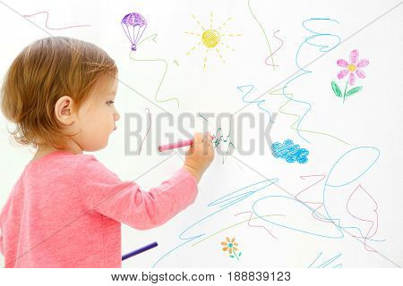 Art concept. Cute little girl drawing on white background with space for design