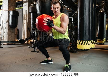 Strong fit sportsman doing squats with weight ball at the gym