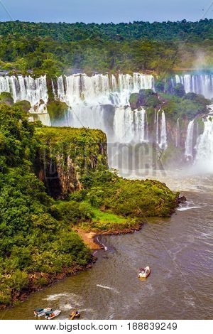 Small boats deliver tourists to waterfalls. Grandiose complex of waterfalls Iguazu Falls National Park. The concept of extreme and exotic tourism