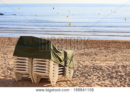 Pile of deck chairs on the empty sea beach