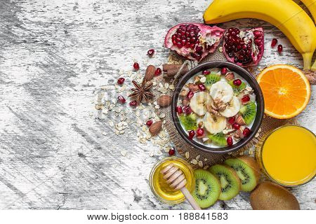 oatmeal porridge with banana kiwi fruit pomegranate cinnamon and nuts in a bowl on white wooden background with egg and orange juice for healthy breakfast. top view with copy space