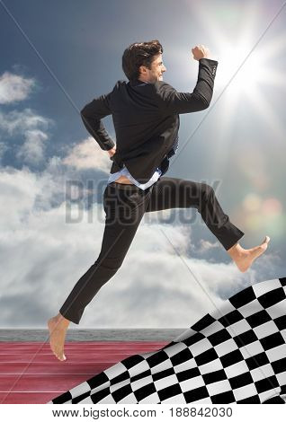 Digital composite of Business man jumping on track behind checkered flag and against sky with sun