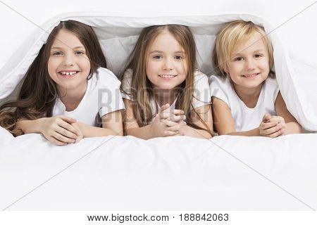 Three happy smiling children under one blanket in bed