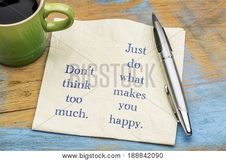 Do not think too much. Just do what makes you happy. Inspirational handwriting on a napkin with a cup of coffee.