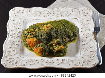 Tandoori chicken with spinach (palak style) on a white dish