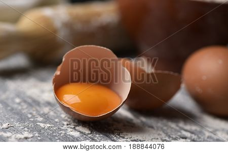 closeup of a cracked egg, a whole egg and a wooden rolling pin on a rustic table sprinkled with flour