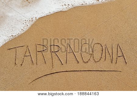 the word Tarragona written in the sand of a beach in Tarragona, Spain