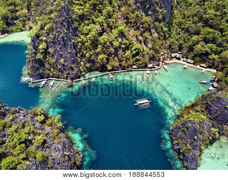 Aerial top view of lagoon with boats surrounded by rocks and turquoise sea. Palawan v
