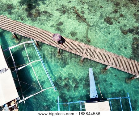 Aerial top view of wooden pier with boats and people. Palawan v