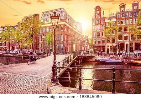 Channel in Amsterdam Netherlands Holland houses under river Amstel. Landmark old european city spring landscape with sunshine.