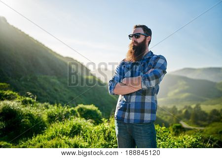 cool bearded guy with sunglasses and blue flannel posing by grassy green hills
