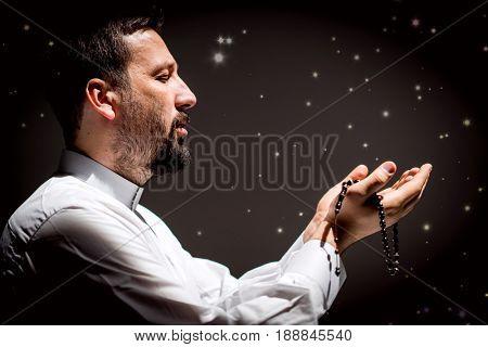 Muslim man praying for god in dark room at ramadan
