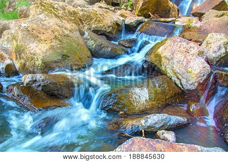 beautiful forest waterfall. on the stony slope runs stormy forest waterfall. in the Sun