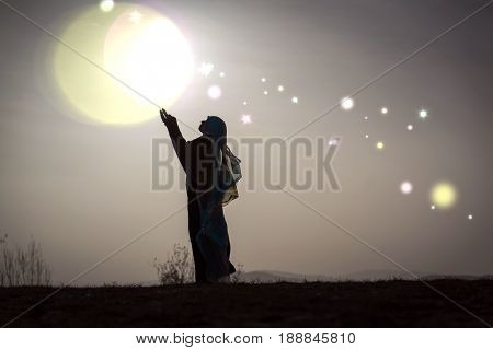 Silhouette woman praying with her hands up