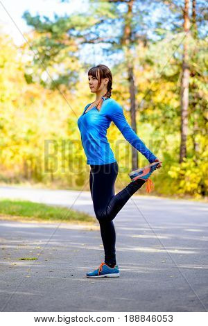 Young Fitness Woman Stretching in the Beautiful Autumn Park at Warm Sunny Day. Active Lifestyle Concept.