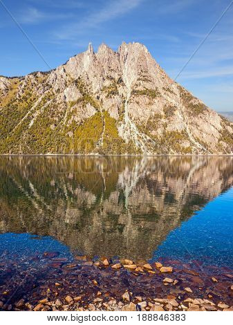The concept of exotic and extreme tourism. Pyramidal mountain in San Carlos de Bariloche. The mirror water of the lake reflects sharp peaks and rocks